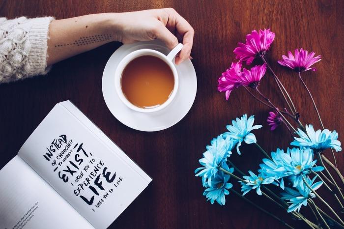 Tasse, Blumen und ein Buch