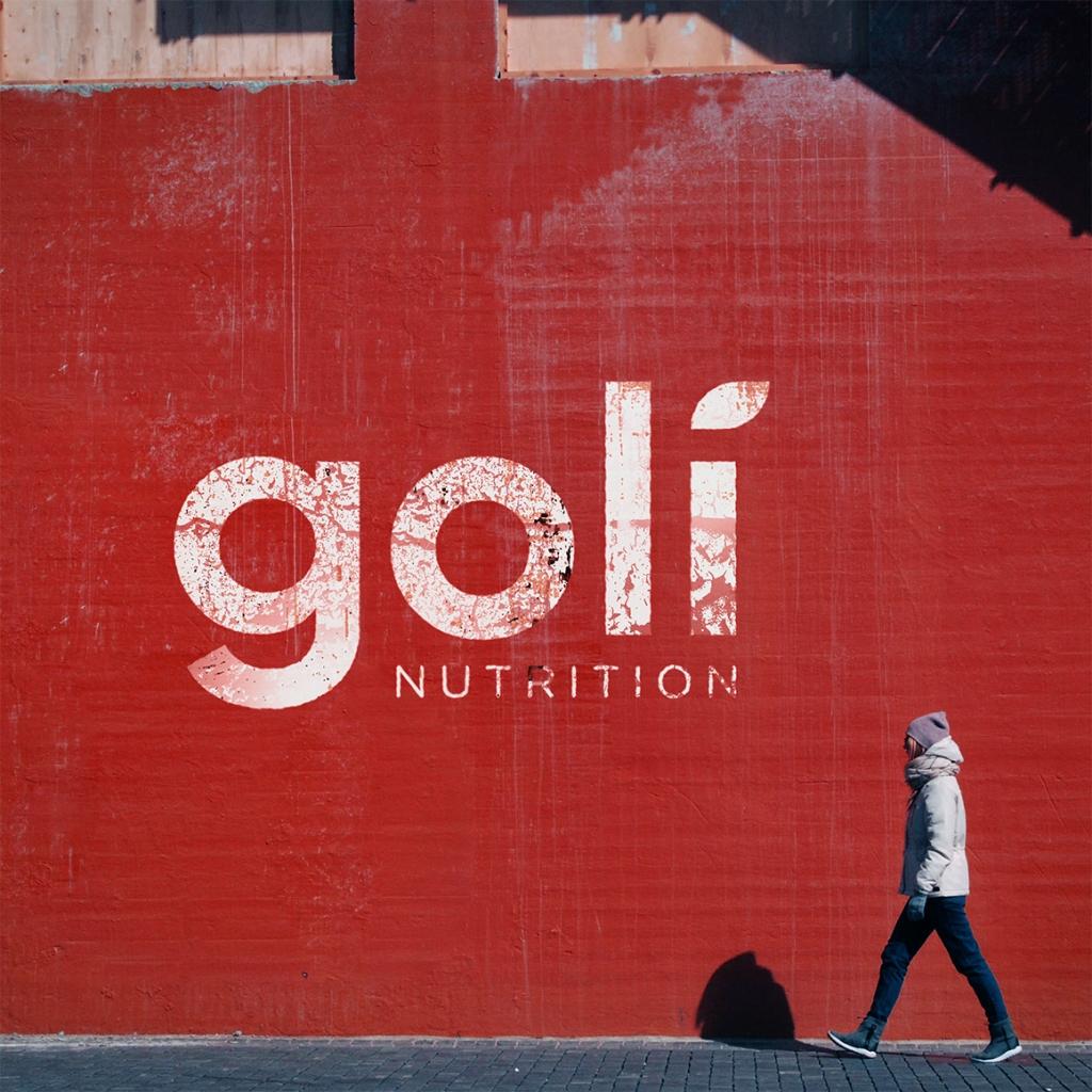 Goli Nutrition Wand mit Frau die vorbei läuft.