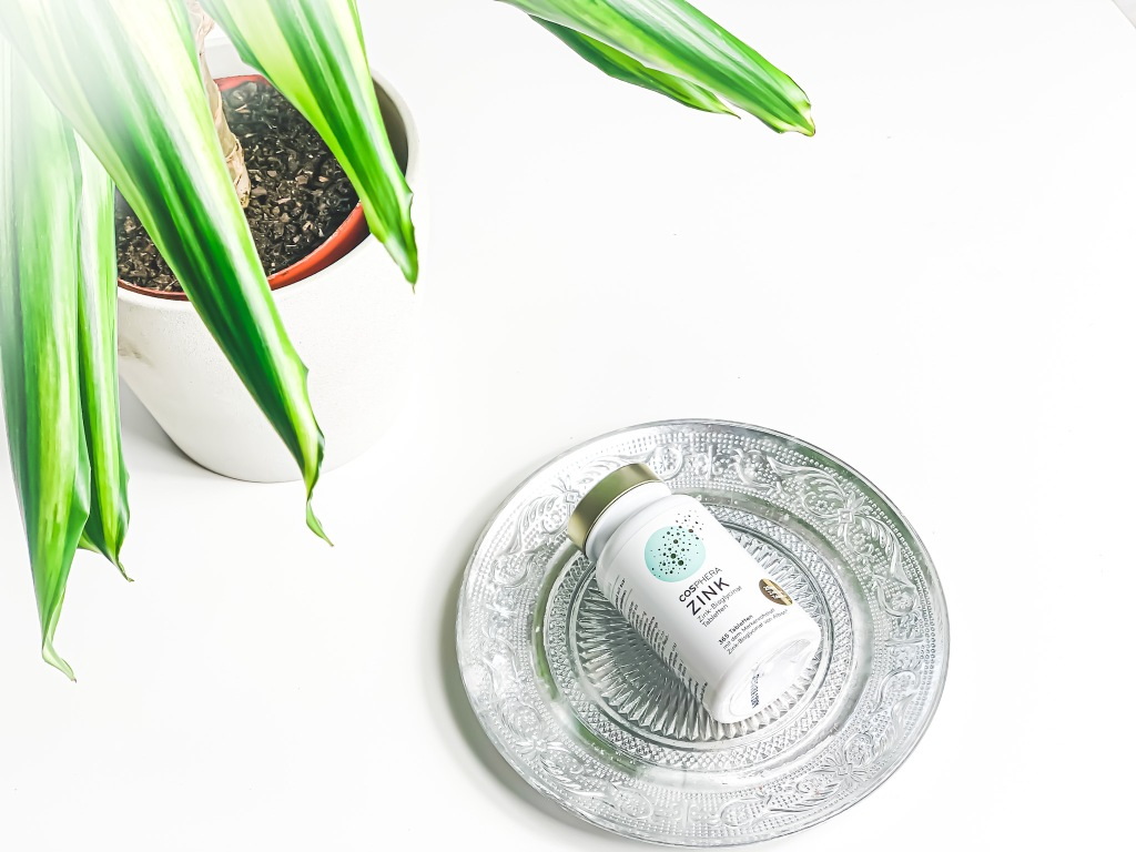 Zink Tabletten von Cosphera auf einem Tablett liegend. Links befindet sich eine grüne Pflanze