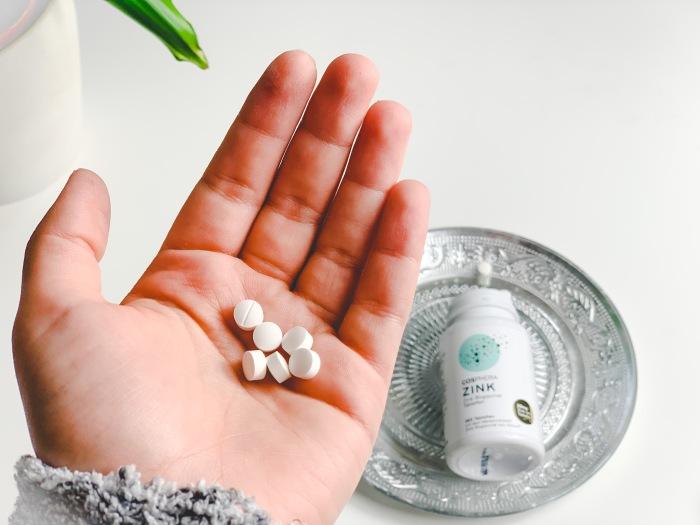 Zink Tabletten liegen In der geöffneten Handfläche. Die Cosphera Zink Verpackung ist im Hintergrund auf einem Tablett zu sehen