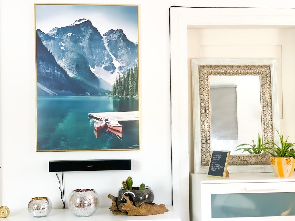 Einrichtungsinspiration. Schränke mit Dekoration und einem großen Wandbild der Berge mit Blick auf den See