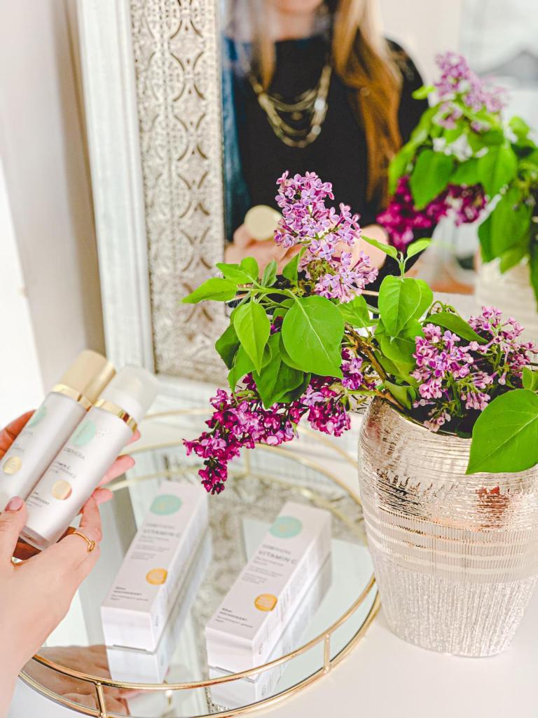 Cosphera Vitamin C Produkte liegen auf einem Tablett auf einer Kommode. Im Spiegel sieht man eine Frau, die weitere Produkte in der Hand hält.